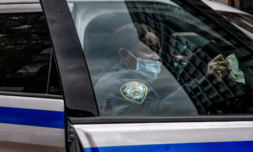 A New York City police officer manually disinfecting her vehicle.